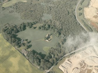 General oblique aerial view of the remains of the priory and the house, taken from the SW.