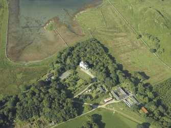 Oblique aerial view centred on the castle and the farmstead, taken from the NE.