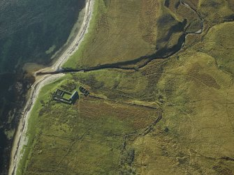 Oblique aerial view centred on the remains of the cottage, rig and sheepfold, taken from the NNE.