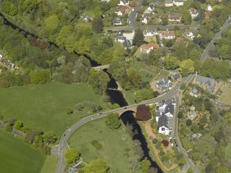 Oblique aerial view centred on the new bridge with the railway bridge, Brig O'Doon Hotel, Burns Monument and Parish Church adjacent, taken from the SSE.