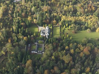 Oblique aerial view centred on the house with the garden adjacent, taken from the E.