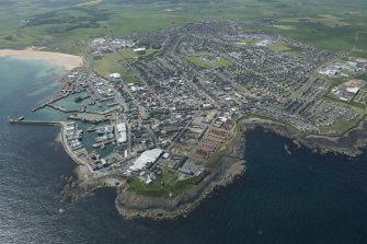 Oblique aerial view of Fraserburgh, Fraserburgh Harbour, Kinnaird Lighthouse and New Lighthouse, looking SW.