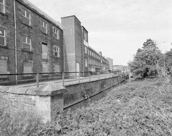 Oblique view from SE along NE side of main range of mill