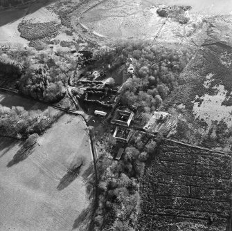 Oblique aerial view centred on the farmstead with the castle adjacent, taken from the N.