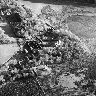 Oblique aerial view centred on the castle and the farmstead, taken from the NW.
