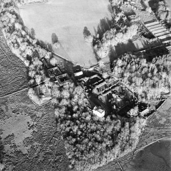 Oblique aerial view centred on the castle and the farmstead, taken from the SW.