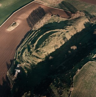 Oblique aerial view centred on the remains of the fort with farmsteading adjacent, taken from the SW.