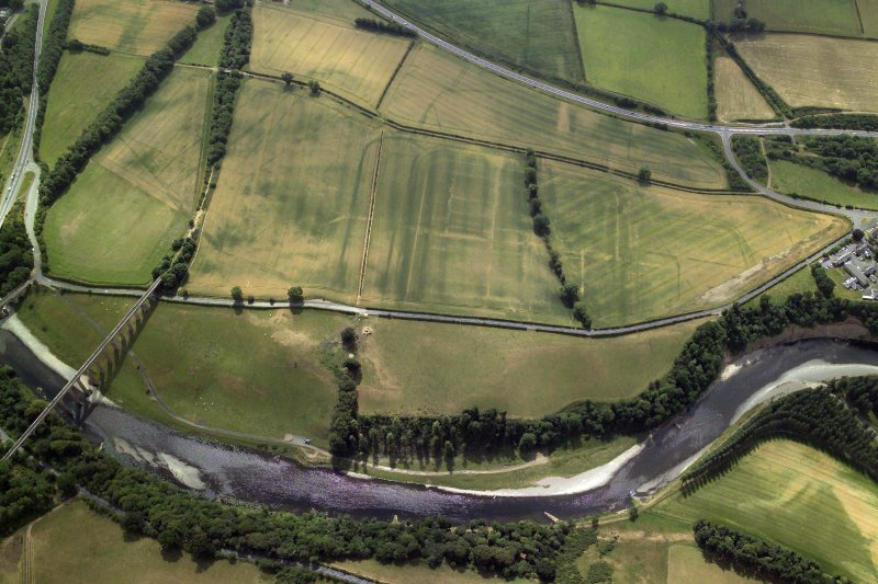 General oblique aerial view centred on the cropmarks of the Roman fort, Roman temporary camps and fort annexes with the railway viaduct adjacent, taken from the N.