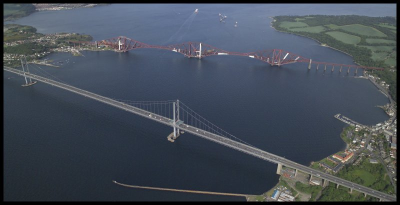 General oblique aerial view centred on the road bridge, suspension bridge, piers and railway bridge, taken from the WSW.