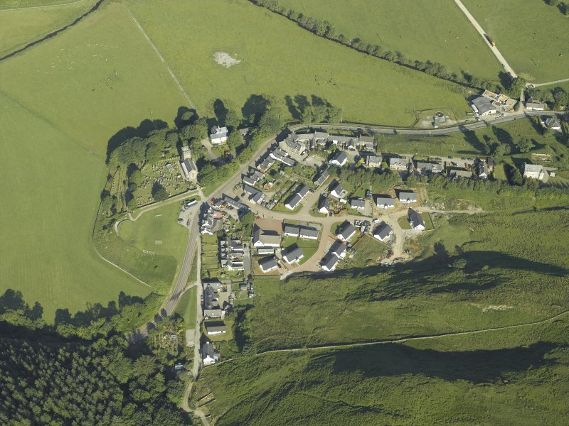 General oblique aerial view of the village, centred on the church, churchyard, burial ground, museum and the remains of the cairn, taken from the ESE.