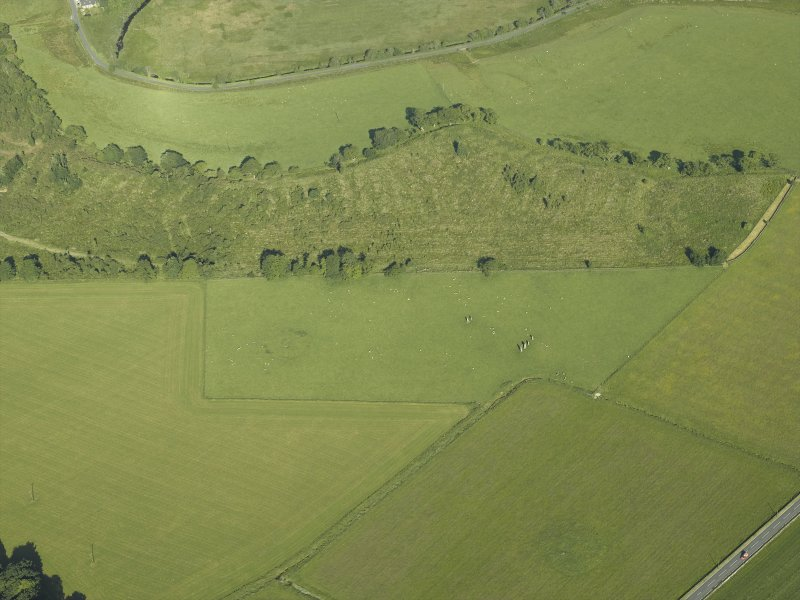 Oblique aerial view centred on the remains of the standing stones, henge and barrow, taken from the ESE.