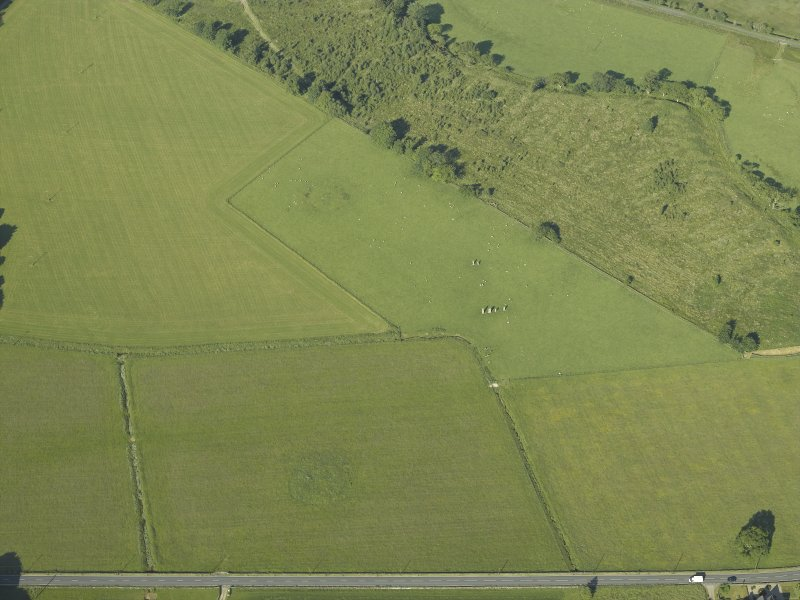 Oblique aerial view centred on the remains of the standing stones, henge and barrow, taken from the ENE.