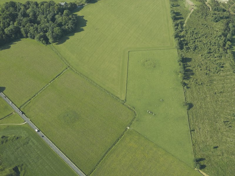 Oblique aerial view centred on the remains of the standing stones, henge and barrow, taken from the NE.