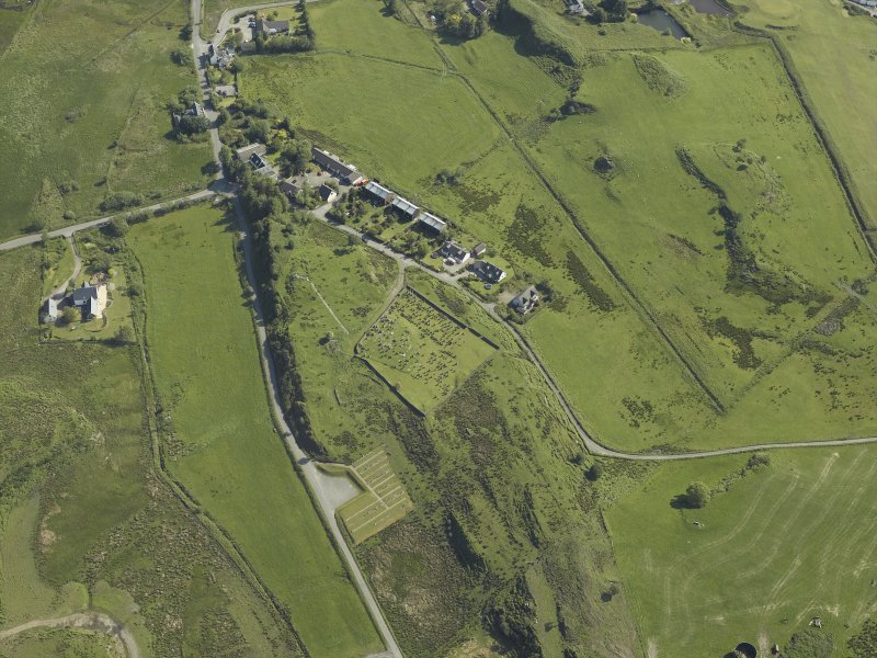Oblique aerial view centred on the church and burial ground with the remains of the township adjacent, taken from the SW.