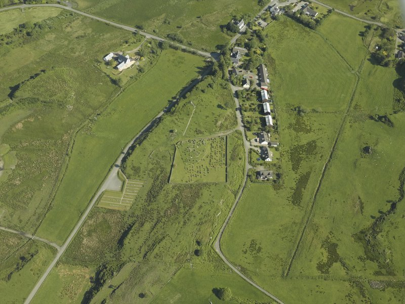 Oblique aerial view centred on the church and burial ground with the remains of the township adjacent, taken from the SSW.