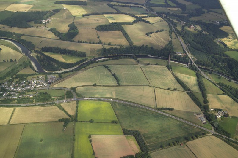General oblique aerial view centred on the cropmarks of the Roman fort, Roman temporary camps and fort annexes with the village, railway viaduct and road bridge adjacent, taken from the S.
