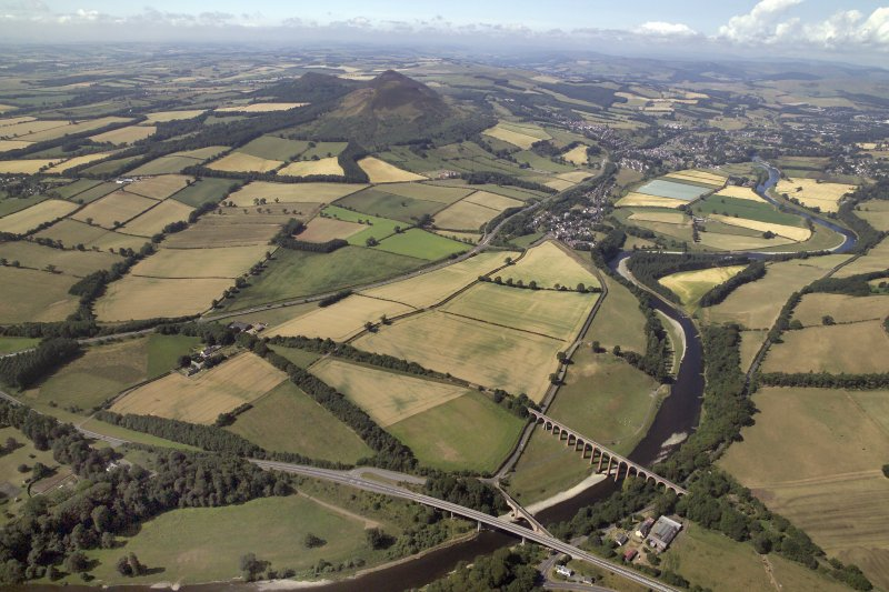 Oblique aerial view centred on the cropmarks of Newstead Roman fort and Roman temporary camps with Melrose town and remains of the Eildon Hill North fort in the distance and the Leaderfoot railway viaduct and road bridge in the foreground, taken from the NE. The viaduct is no longer in use.