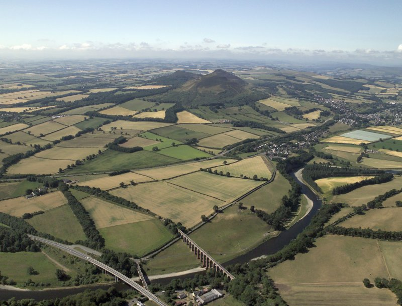 General oblique aerial view centred on the cropmarks of the Roman fort and Roman temporary camps with the town, village and remains of the fort in the distance and the railway viaduct and road bridge in the foreground, taken from the NE.
