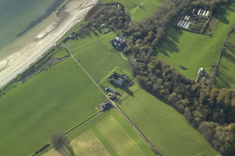 Oblique aerial view centred on the remains of the tower-house with the country house adjacent, taken from the ENE.