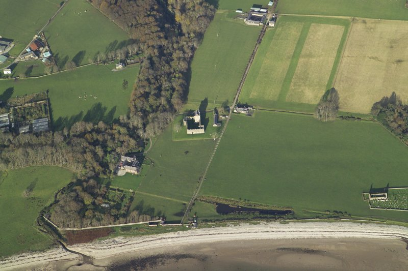 General oblique aerial view centred on the remains of the tower-house with the country house and remains of the church and burial ground adjacent, taken from the SW.