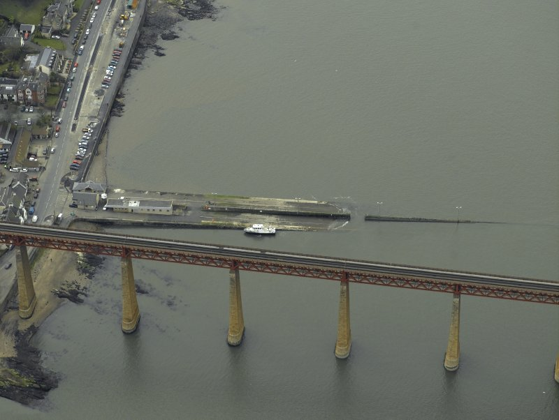 Oblique aerial view centred on the pier, slipway and lifeboat station with the railway bridge adjacent, taken from the NE.