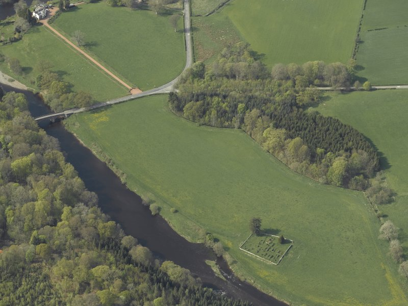 Oblique aerial view centred on the graveyard and the ruins of the church with the road bridge adjacent, taken from the SE.