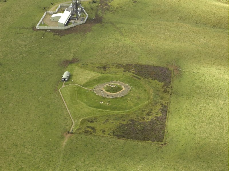 Oblique aerial view centred on the remains of henge and cairn, taken from the SSW.