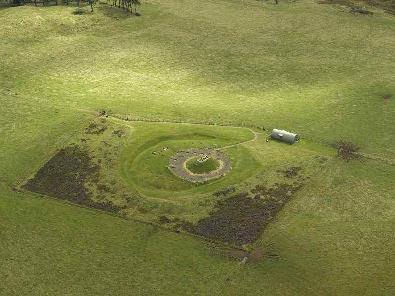 Oblique aerial view centred on the remains of henge and cairn, taken from the NW.