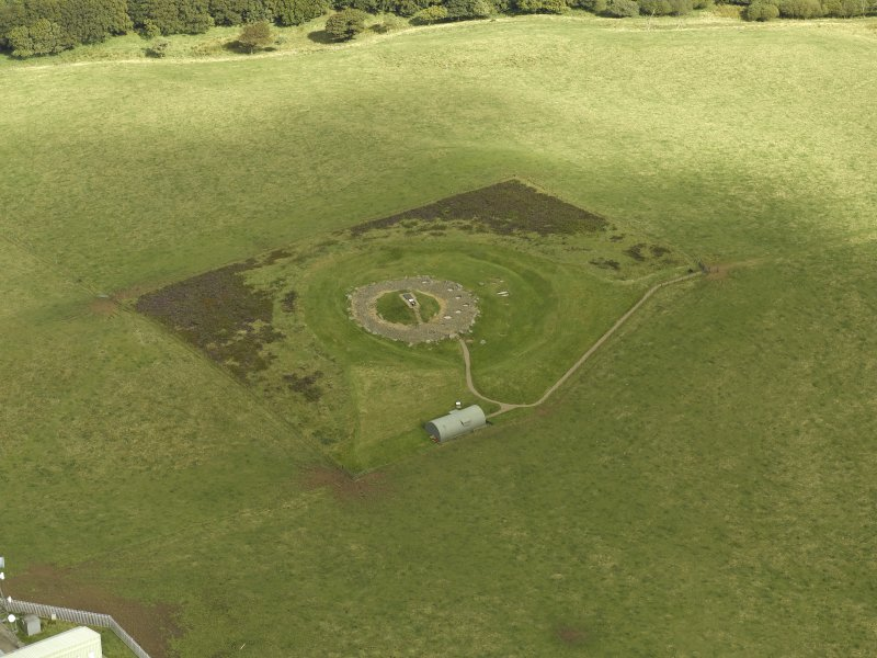 Oblique aerial view centred on the remains of henge and cairn, taken from the NE.