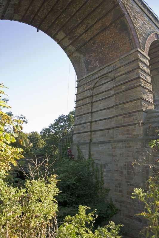 General  view from SW,  of drill operator abseiling whilst test drilling lower pier of viaduct.