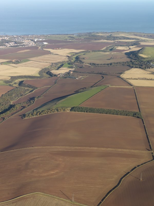 General oblique aerial view of the soilmarks of the fort of The Chesters, Spott, with the coast in the distance, taken from the SW.
