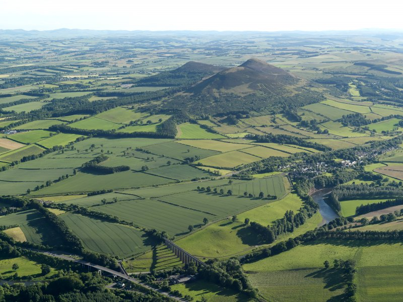 General oblique aerial view looking across the bridge, viaduct, village and site of the Roman fort  towards the fort and Eildon Hills, taken from the NNE.