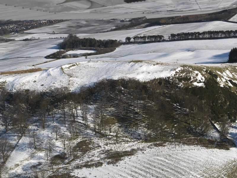 Oblique aerial view centred on the remains of the fort and rig, taken from the W.