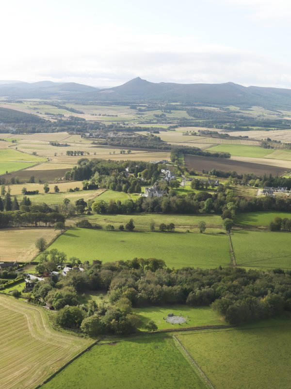 General oblique aerial view of the remains of the recumbent stone circle and enclosed cremation cemetery at Loanhead of Daviot with Mither Tap of Bennachie in the distance, taken from the SW.