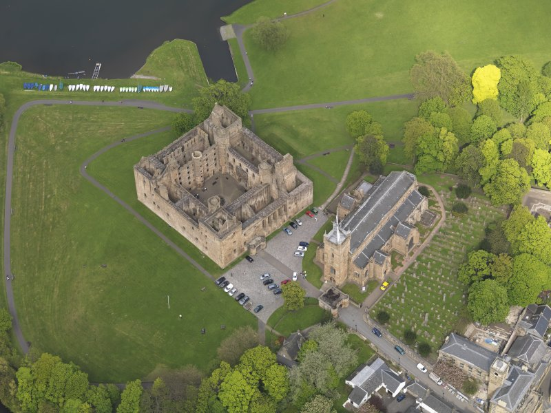 Oblique aerial view centred on the Palace with the parish church adjacent, taken from the SW.