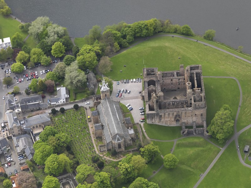 Oblique aerial view centred on the Palace with the parish church adjacent, taken from the E.