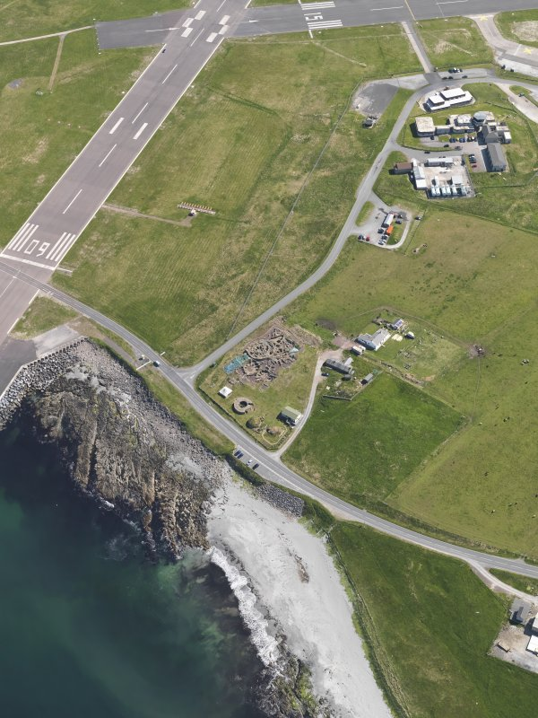 Oblique aerial view centred on the excavated broch and settlement at Old Scatness, Sumburgh, and the visitor attraction, taken from the SW.