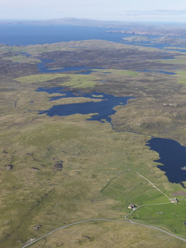 General oblique aerial view with Brouster in the foreground and the Loch of Voxterby and Brace Field in the middle distance and Burrafirth beyond, looking N.