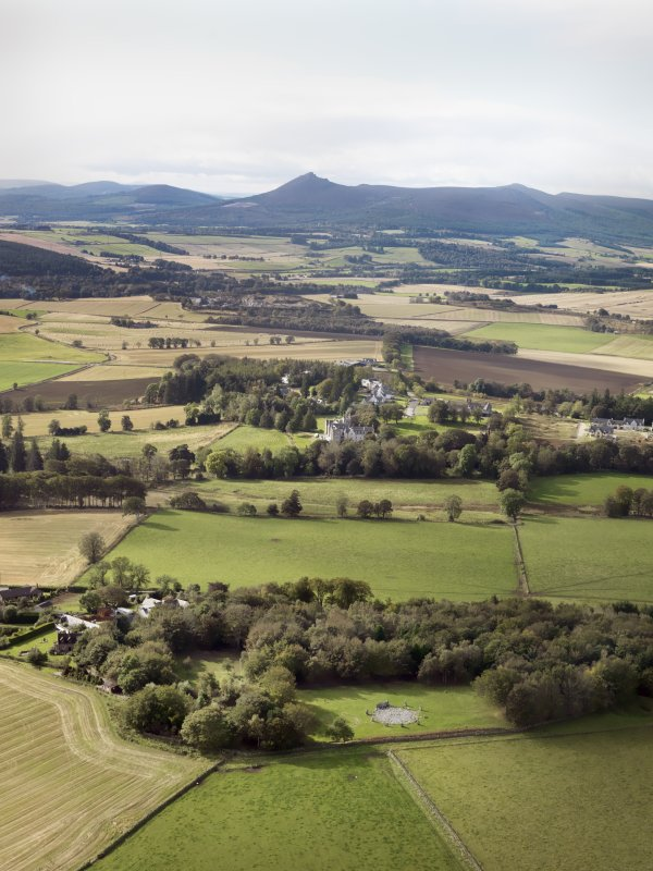 General oblique aerial view of the remains of the recumbent stone circle and enclosed cremation cemetery at Loanhead of Daviot with Mither Tap of Bennachie in the distance, taken from the NE.
