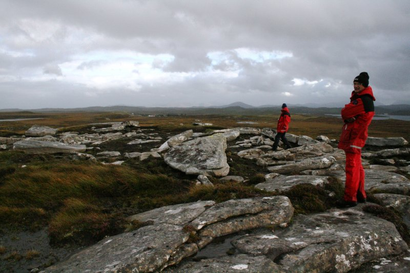 View from N showing fallen monoliths on W half of circle, with Mr Ian Parker and Mr Stratford Halliday, both RCAHMS.