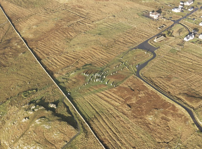 Oblique aerial view centred on the stone circle and stone row, the remains of the buildings and lazy beds at Calanais, taken from the SE.