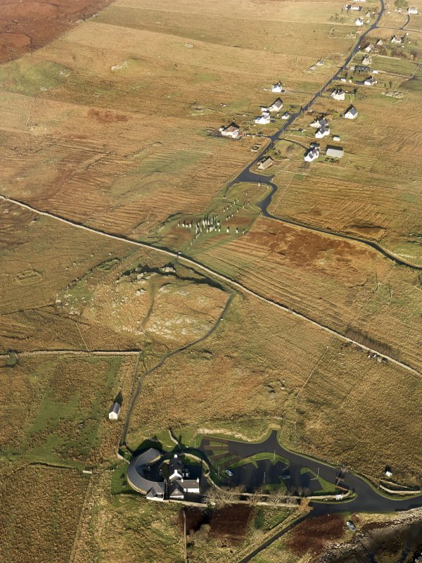 General oblique aerial view centred on the stone circle and stone row, the remains of the buildings and lazy beds at Calanais with the visitor centre in the foreground, taken from the S.