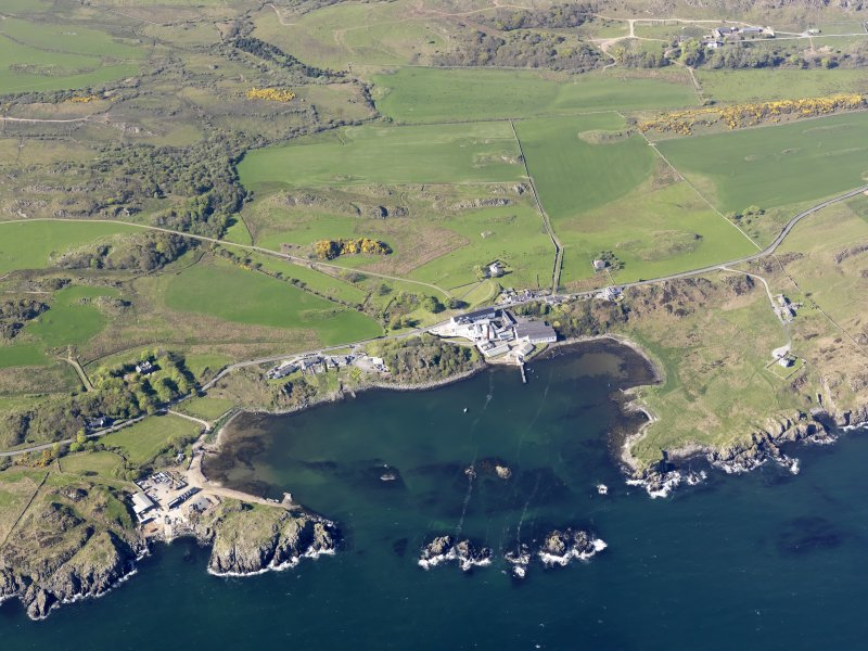 General oblique aerial view of Lagavulin Distillery with the remains of the fort and Dunivaig Castle adjacent, taken from the SSE.