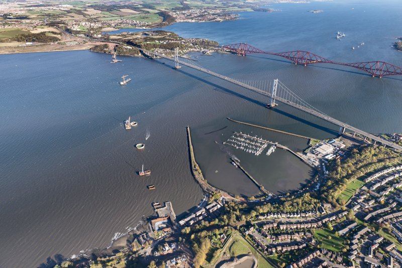 General oblique aerial view of the River Forth showing the construction site of the new Queensferry Crossing, the Forth Road and Rail bridges and Port Edgar looking to the NE.