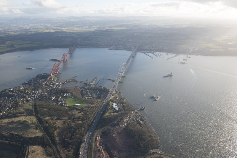 Oblique aerial view of the construction of the Queensferry Crossing, the Forth Road Bridge and Forth Rail Bridge, looking SSW.