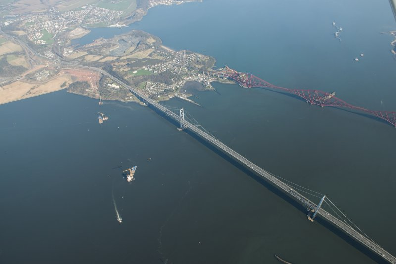 Oblique aerial view of the Forth Bridge, Forth Road Bridge and Queensferry Crossing construction, looking to the ENE.