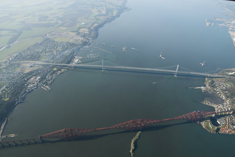 Oblique aerial view of the Forth Bridge, Forth Road Bridge and Queensferry Crossing construction, looking to the WSW.