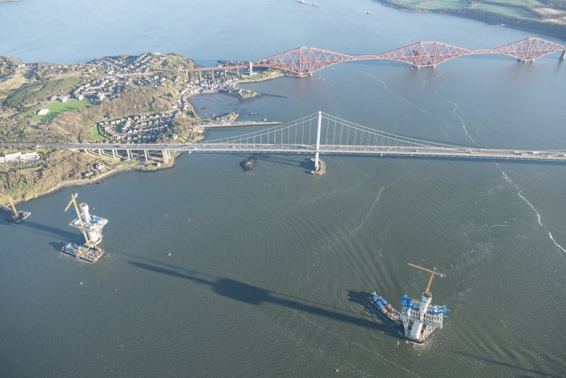 General oblique aerial view of the Forth Bridge, the Forth Road Bridge and the construction of the Queensferry Crossing, looking E.