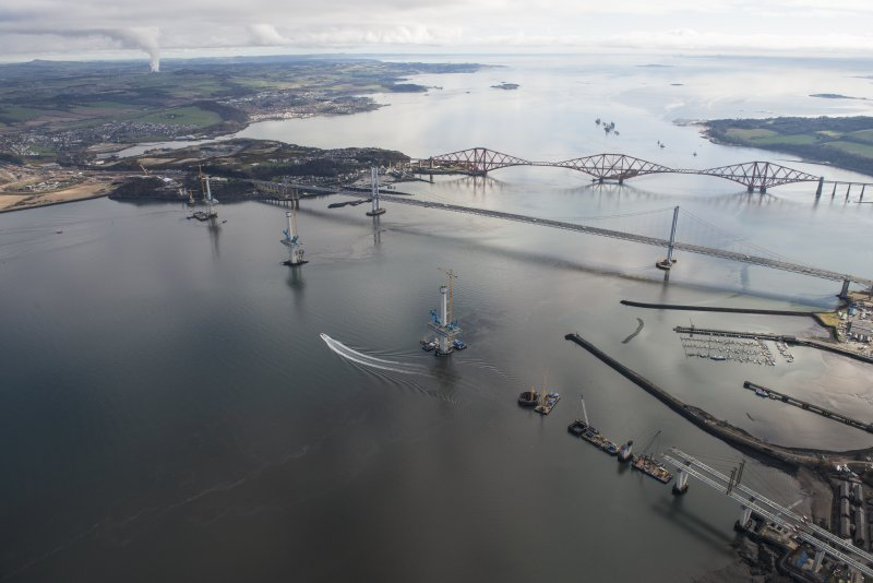 Oblique aerial view of the construction of the Queensferry Crossing with the Forth Road Bridge and the Forth Bridge beyond, looking E.
