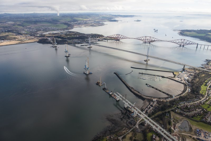 Oblique aerial view of the construction of the Queensferry Crossing with the Forth Road Bridge and the Forth Bridge beyond, looking ENE.